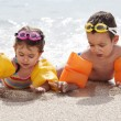 Постер, плакат: Children on beach in inflatable water armbands and goggles