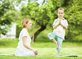 Yoga in park. mother and son — Foto de Stock