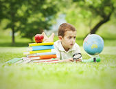 Boy lying in park with pile of books, globe, magnifying glass — Stock Photo