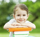 Little girl with pile of books — Stock Photo