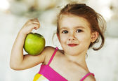 Little girl holding apple on her bicep — Stock Photo