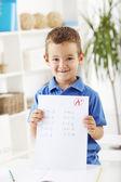 šťastný školák drží zkoušku papíru — Stock fotografie