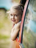 Portrait of a cute little girl peeking from car — Stock Photo