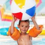 Мальчик улыбается и играет с мячом — Стоковое фото