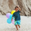 Little boy running with bunch of ballons on the beach — Stock Photo