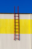 Red ladder on a white-yellow wall. — Stock Photo