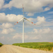 The wind turbine, gravel driveway in the foreground. — Stock Photo