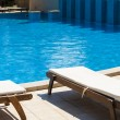 Постер, плакат: Edge of swimming pool Sun loungers by the pool