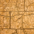Cracked plaque with Latin inscriptions and Roman letters. — Stock Photo