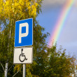 Rainbow over a parking space for the disabled person. — Stock Photo