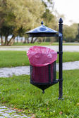Trash basket with pink plastic bag. — Stock Photo