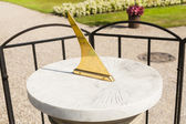 Sundial with marble base standing in garden. — Stock Photo