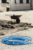 Blue garden hose lying on the gravel path. — Stock Photo