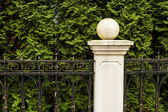 A fragment of a fence with a post with the sphere. — Stock Photo