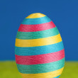 Striped rainbow coloured big easter egg on green and blue backgr — Stock Photo