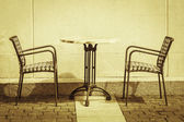 Two chairs and a table, symmetrical composition. — Stock Photo