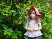 Little girl in a red cap standing in the woods — Stock Photo