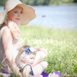 Beautiful blond hair mother and daughter near the river — Stock Photo #27716383