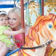 Happy mother and daughter on carousel — Stock Photo