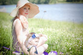 Beautiful blond hair mother and daughter near the river — Stock Photo