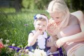 Vackra blonda hår mor och dotter sitter i gräset — Stockfoto