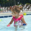 Cute baby girl is having fun in the pool — Stock Photo