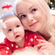 Christmas baby girl with blond hair mother — Stock Photo