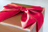 Gold present with red bow -isolated — Stock Photo