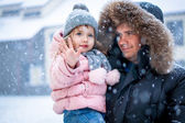 Father and daughter enhoying snow blowing at daytime — Stock Photo
