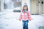 Cute baby girl in pink jacket and grey hat enjoying first snow b — Stock Photo