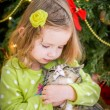 Cute baby girl in green dress is kissing a cat near christmas tree — Stock Photo #37198875