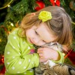 Cute baby girl in green dress is kissing a cat near christmas tree — Stock Photo #37198879