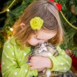 Cute baby girl in green dress is kissing a cat near christmas tree — Stock Photo #37198889
