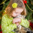Cute baby girl in green dress is kissing a cat near christmas tree — Stock Photo #37198897