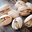 Close-up of roasted pistachios on wooden background — Stock Photo