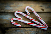 Candy cane on wooden background — Stock Photo