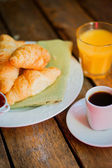 Black croissants with black coffee on wooden background — Stock Photo