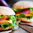 Closeup of home made burgers on wooden background — Stock Photo #39190199