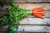 Farm raised organic carrots on wooden background — Stock Photo