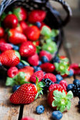 Mix of fresh berries in a basket on rustic wooden background — Stock Photo