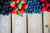 Mix of berries on rustic wooden background — Stock Photo