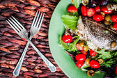 Baked seabass with tomatoes and basil on rustic wooden background — Stock Photo