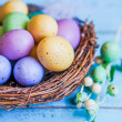 Stock Photo: Easter eggs in nest on blue wooden background