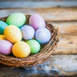 Stock Photo: Easter eggs in nest on rustic wooden background