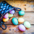 Stock Photo: Easter eggs in basket on rustic wooden background