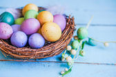 Easter eggs in the nest on blue wooden background — Stock Photo