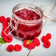 Raspberry jam in a jar on wooden background — Stock Photo