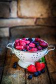 Frozen berries on rustic wooden background — Stok fotoğraf