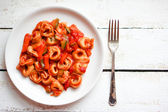 Tortellini primavera parmesan in marinara sauce on wooden rustic — Stock Photo