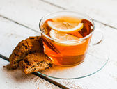 Tea cup with lemon and cookies on rustic wooden background — Stock Photo